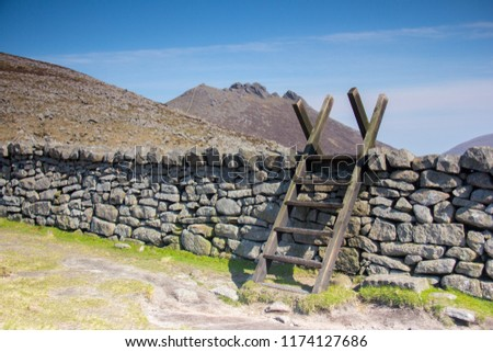 Wooden stile over a dry stone wall in the unique landscape. Mournes moutains, Northern Ireland - Shutterstock ID 1174127686