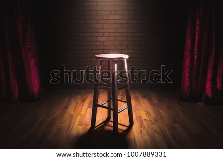 wooden stool on a stand up comedy stage with reflectors ray, high contrast image Stockfoto ©