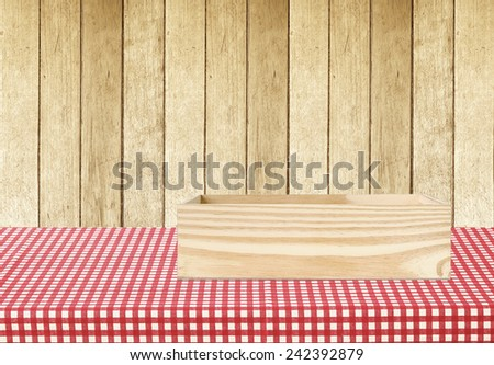 Wooden storage box on table covered with red checked tablecloth over wood wall background, for product display montage background