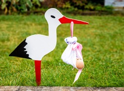 Wooden stork figure outside house to let bypasser know of the happy arrival of newborn girl seen by the pink ribbon.
