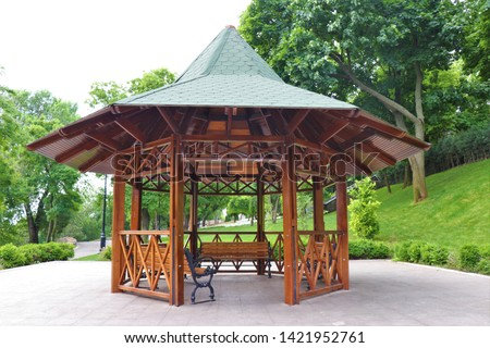 Wooden structure gazebo in a garden park. Relaxing place with a pavilion with bench. Full of green plants and trees, a good place where spend time to rest.