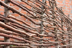 Wooden stylized fence with intertwined dry branches on a background of a brick wall as a defocused pattern in a rustic style