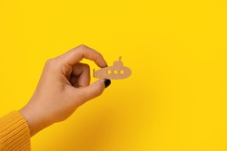 wooden submarine in hand over yellow background