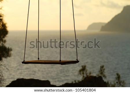 Wooden swing chair near the ocean
