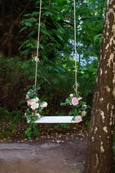 Wooden swing in playground outdoors. Empty swing placed in park. Wedding swing decorated with flowers roses. Garden swing hanging  from a large tree on green grass background. Garden decor. Romance