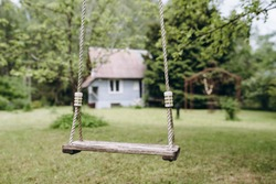 Wooden swing in the garden or park in the front of blurred house. Natural wood and rope. Around the greenery: lawn, trees. The swing is empty, in the center of the frame. Place of harmony and peace