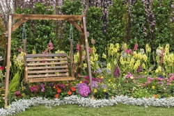 Wooden swing seat in flower garden