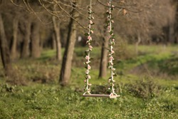 Wooden swing with flowers in park.