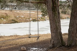 Wooden swings on a tree branch on a mountainside on springtime with icy river on the background.