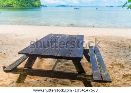 wooden table and benches on a sandy beach on the background of the sea