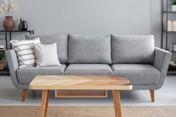 Wooden table and big grey couch with pillows in living room of trendy apartment, real photo with copy space on the wall