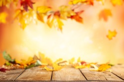 Wooden table and blurred Autumn background. Autumn concept with red-yellow leaves background.