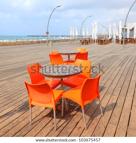 Wooden table and orange chairs on the wooden embankment of the seaside background