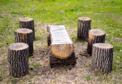 Wooden table and stools made from tree logs outdoors