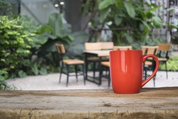wooden table and table cloth over blurred background of chair and table in the outdoor garden for present product.