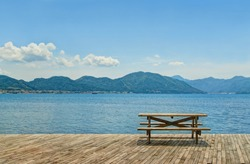 wooden table and two benches for picnic standing on wooden flooring by sea on sunny day facing green mountainous islands near Marmaris,  Turkey