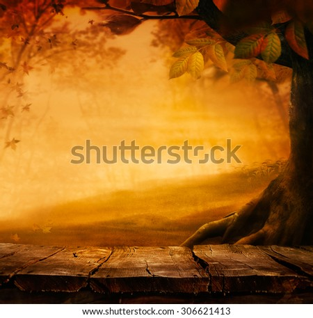 Wooden table. Autumn design with leaves falling in  forest and empty display. Space for your montage. Season fall background