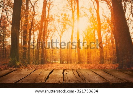 Stock Photo Wooden table. Autumn design with leaves falling in  forest and empty display. Space for your montage. Season fall background