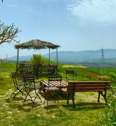 Wooden table, chairs on a sunny terrace against the backdrop of a mountain and green landscape on a colorful spring day. Concept: relaxation and ecotourism. Barbare Tekirdag Wine House.