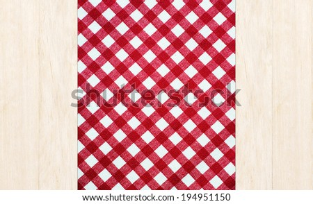 Wooden table covered with red checked tablecloth. top view.