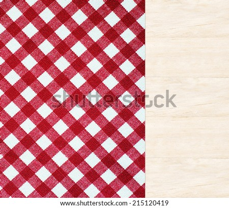 Wooden table covered with red checked tablecloth, top view, background, display, template