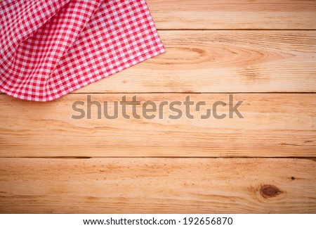 Wooden table covered with tablecloth. View from top. Empty tablecloth for product montage. Free space for your text