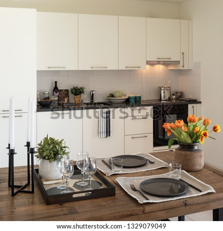Wooden table detail with plates, cutlery and bunch of orange tulips. Modern design kitchen. Nobody inside #1329079049