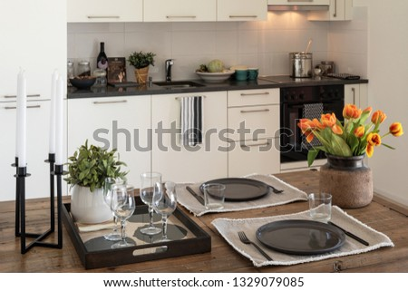 Wooden table detail with plates, cutlery and bunch of orange tulips. Modern design kitchen. Nobody inside #1329079085