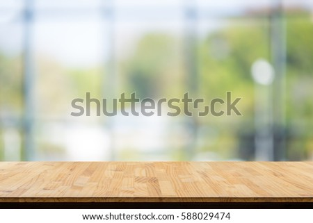 wooden table in front of abstract Blur white green background from office window