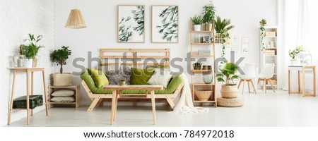 Wooden table in front of green couch with cushions in floral living room interior with leaves posters and suitcase on shelf #784972018