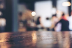 Wooden table in modern loft cafe with blur bokeh vintage background