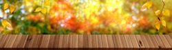 wooden table in the garden, beautiful blurred natural landscape in the background, long panorama, the concept of a cozy autumn mood, blank for the designer