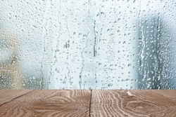 Wooden table near window on rainy day