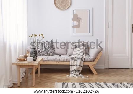Wooden table next to beige settee with blanket in bright living room interior with poster. Real photo