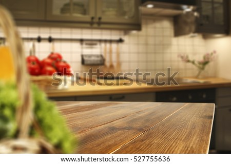 Wooden table of free space in kitchen and blurred vegetables