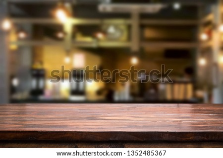 Wooden table on abstract blurred interior restaurant background and free space for decoration display or montage products. #1352485367