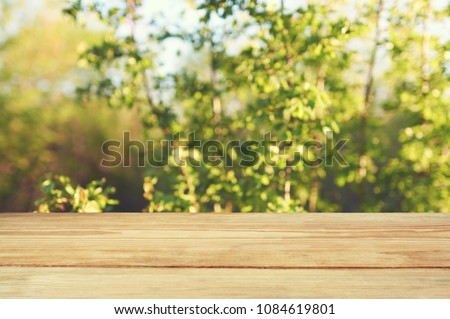 Wooden table on blur nature tree green background. #1084619801