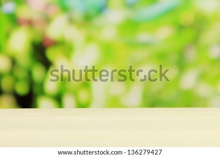 Wooden table on bright green background