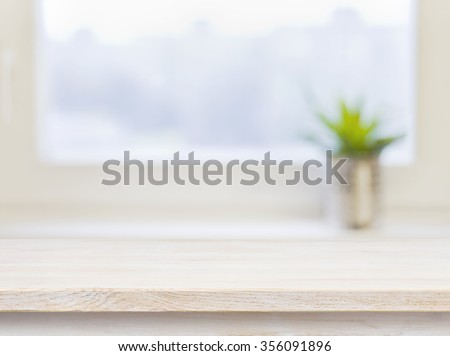 Wooden table on defocuced winter window background