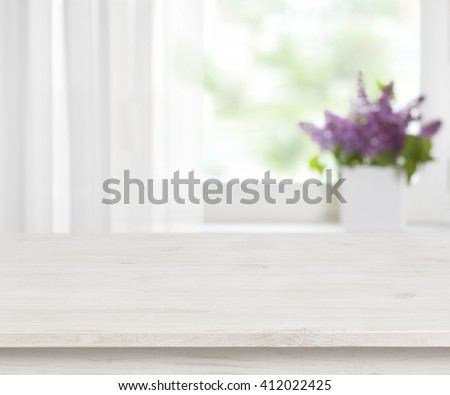 Wooden table on defocused window with purple flower pot background