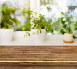 Wooden table on defocused windowsill background