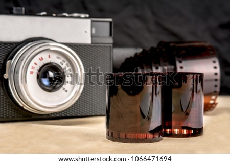 Wooden table on it a camera and a film for him #1066471694