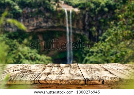 Wooden table on the background of a waterfall on a summer day