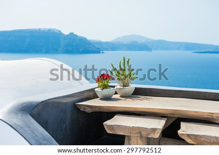 Wooden table on the terrace with sea view. Santorini island, Greece. Selective focus #297792512