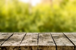 Wooden table or bench on green blurred background. Outdoors