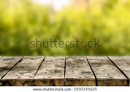 Wooden table or bench on green blurred background. Outdoors Сток-фото ©