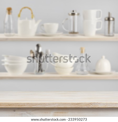 Wooden table over background of shelves with kitchen utensils