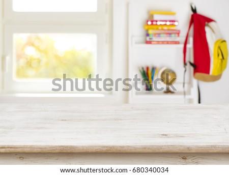 Wooden table over blurred background of junior schoolchild room interior