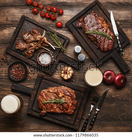 Wooden table served with various grilled meat, vegetables and glasses of beer. Striploin steak, ribeye steak and lamb ribs on wooden cutting boards. Top view