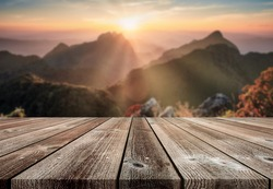Wooden table top on blurred sunset on mountain in wildlife sanctuary at Doi Luang Chiang Dao national park background
